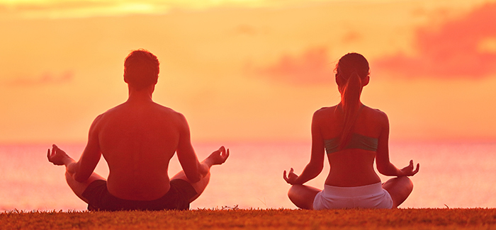 Meditation yoga couple meditating at serene beach sunset. Girl a