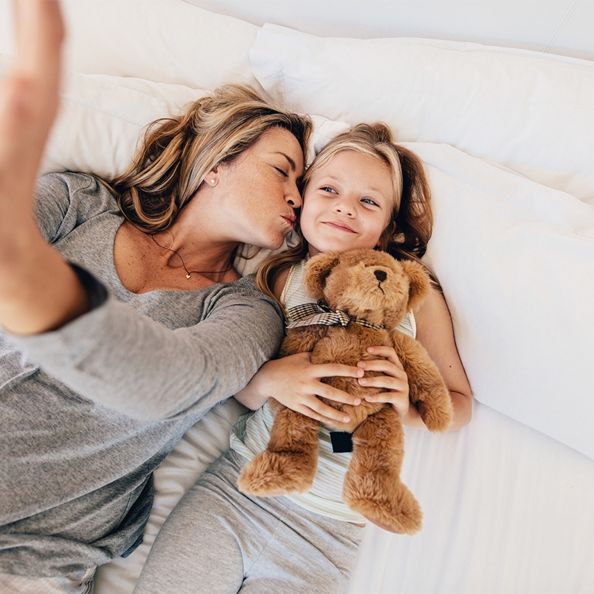 Mother and daughter lying on bed and taking self portrait with mobile phone. Woman kissing her daughter and taking self portrait.